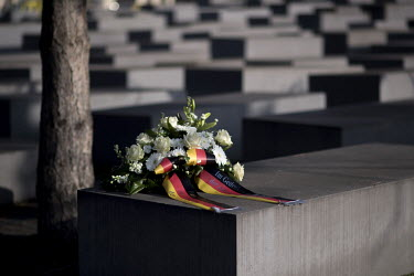 A bouquet of flowers with German national flag ribbons left on a stele of the Holocaust Memorial on Holocaust Memorial Day 2021.