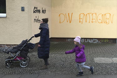 A woman and her child pass graffiti protesting the investors and property companies that are gentrifying the city.