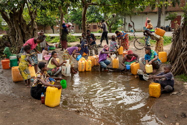 People collecting contaminated water from a muddy puddle created by a burst mains water supply. The water is being used for drinking water and for bathing, people aren't boiling it and in some cases d...