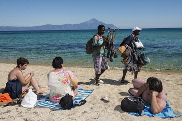 African migrants selling countefeit luxury brand bags and African handicrafts to tourists on the beach.