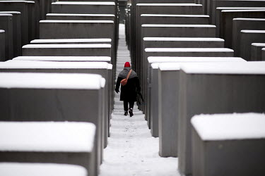 A vistor walks through snow that has fallen on the Stele of the Holocaust Memorial.