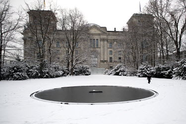 Snow covers the Memorial to the Sinti and Roma of Europe Murdered under National Socialism near the Reichstag.