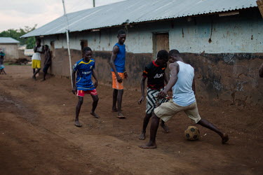 Noah and Vincent Oletey, face off against each other during an evening game of football with friends in the village of Kpando Torkor.  Boat crew Vincent (14) and his brother Noah Oletey (12) spend up...