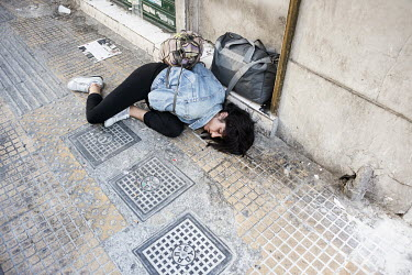 An intoxicated drug user lies on the pavement near Omonia Square.