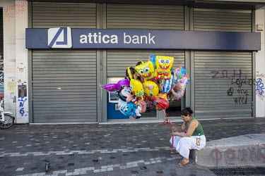 A Roma woman selling novelty balloons in front of a branch of the Attica Bank.