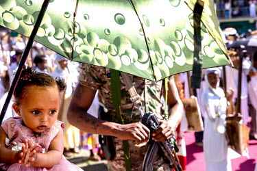 A toddler under the shade of a parasol and a soldier at the Timkat procession, celebrating the baptism of Jesus and the Orthodox Epiphany. The official slogan for the 2021 celebrations was 'Ethiopia's...