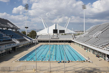 People using a swimming pool that was built for the 2004 Athens Olympics.