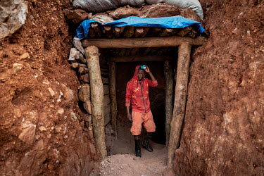 A man in the entrance shaft of an informal gold mine.