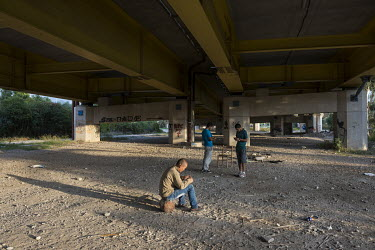 Afghan migrants sit beneath the Rio - Antirrio bridge. They hope to get on board a ship to Italy one day, and begin a new life in England. Meanwhile they live in abandoned houses near the bridge.