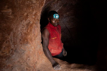 A man in the shaft of an informal gold mine.