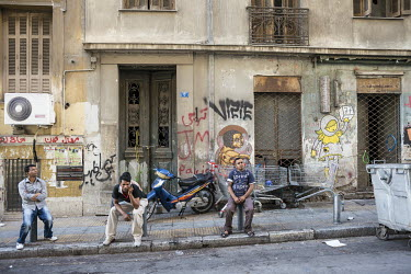 South Asian migrants sit outside a graffiti coved building.
