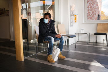 Julien Apedjinou in the waiting room ahead of a medical appointment. He suffers from sickle cell disease and has suffered and continues to suffer many of the condition's wide-ranging impacts, includin...