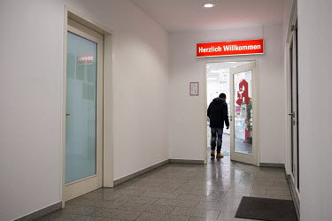 Julien Apedjinou entering a pharmacy to fill a prescription for painkillers. The 27 year-old walks with difficulty due to pain in his hips. He suffers from sickle cell disease and has suffered and con...