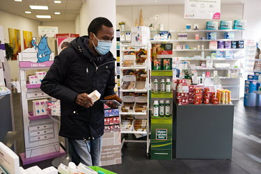 Julien Apedjinou in a pharmacy collectingl a prescription for painkillers. The 27 year-old walks with difficulty due to pain in his hips. He suffers from sickle cell disease and has suffered and conti...