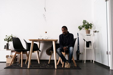 Julien Apedjinou in his home in Bielefeld. He suffers from sickle cell disease and has suffered and continues to suffer many of the condition's wide-ranging impacts, including severe pain crises resul...