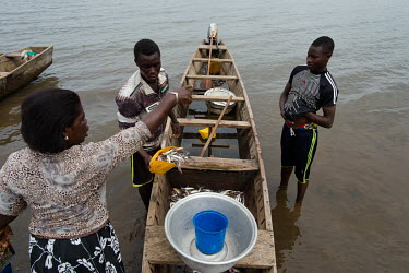 A fish vendor buying fish caught by fisherman Jonas Asideka and crew Vincent Oletey with his brother Noah (not pictured) after a fishing trip on Lake Volta.  Brothers Vincent (14) and Noah (12) spend...