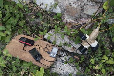 Mobile phones belonging to a group of Algerian transit migrants who are camped in a decrepit abandoned factory building, are being charged from an illegal link to a high voltage cable. The migrants ar...