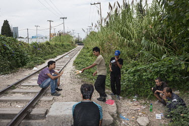 A group of Afghan migrants eat beside the railway tracks that lead to the port where they hope to stowaway on a boat to Italy.