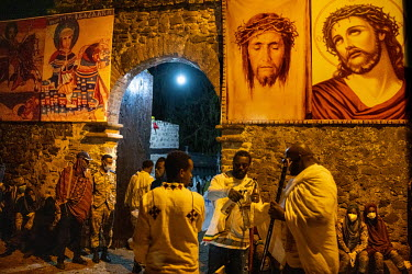 Images of Jesus Christ hang from a gateway where pilgrims are sprayed with sanitisers before passing through during Timkat, celebrating the baptism of Jesus and the Orthodox Epiphany. The official slo...