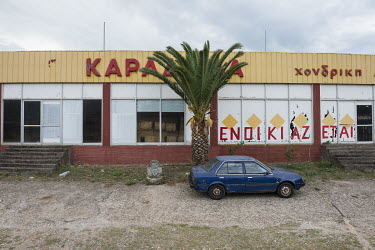 The premises of a closed down business with 'to let' (Enoikiazetai) painted on its windows.