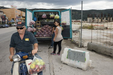A couple selling apples from a van parked at a roadside.