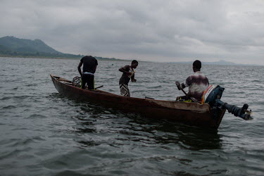 Vincent (14, left) and Noah Oletey (12), together with boat pilot Jonas Asideka, setting fish traps in Lake Volta an hour offshore of the village of Kpando Torkor.  Brothers Vincent and Noah spend up...