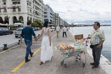 A couple walk hand-in-hand along the sea front where a man is selling bread rings from a shopping trolly at half a Euro each.