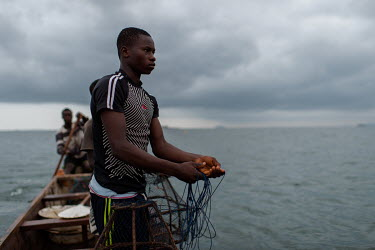 Vincent Oletey (14), hauls up fish traps while working as boat crew on Lake Volta alongside his brother Noah (12) and boat pilot Jonas Asideka.  Vincent and Noah spend up to six nights a week working...