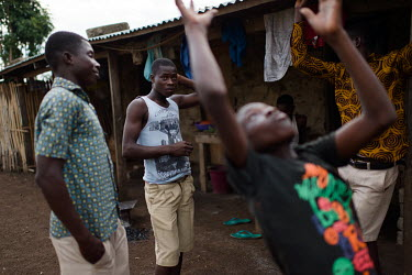Vincent Oletey watching younger boys toss a ball as he hangs out with friends in the village of Kpando Torkor.  Boat crew Vincent (14) and his brother Noah Oletey (12) spend up to six nights a week wo...