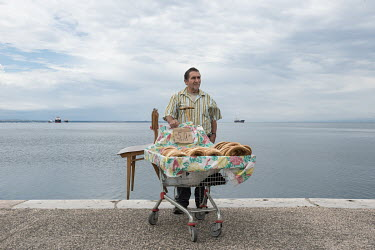 A man on the sea front selling bread rings from a shopping trolly at half a Euro each.