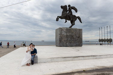 A couple take a selfie photograph in front of the equine statue of Alexander The Great.