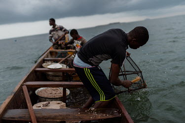 Vincent Oletey (14), cleans a fish trap while working as boat crew on Lake Volta alongside his brother Noah (12) and boat pilot Jonas Asideka.  Vincent and Noah spend up to six nights a week working o...