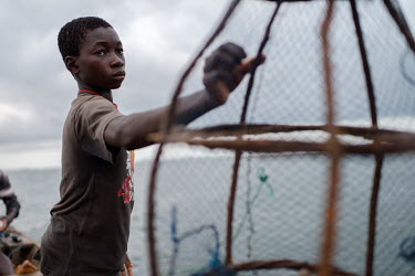 Noah Oletey handing a fish trap to his older brother, Vincent, an hour offshore on Lake Volta.  Boat crew Vincent (14) and Noah Oletey (12) spend up to six nights a week working on fishing canoes on L...