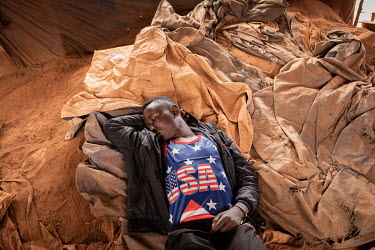 A man sleeping on the surface at an informal gold mine.
