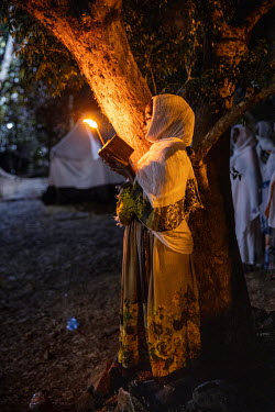 A pilgrim reads a prayer book and burns a candle during a night time vigil during Timkat, celebrating the baptism of Jesus and the Orthodox Epiphany. The official slogan for the 2021 celebrations was...