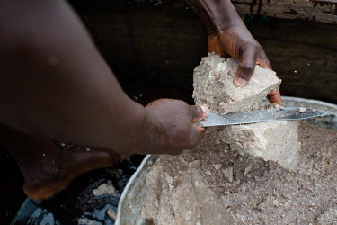 Vincent Oletey cutting bait, made from cooked maize flour and oil, for fish traps used during a fishing voyage on Lake Volta.  Boat crew Vincent (14) and Noah Oletey (12) spend up to six nights a week...