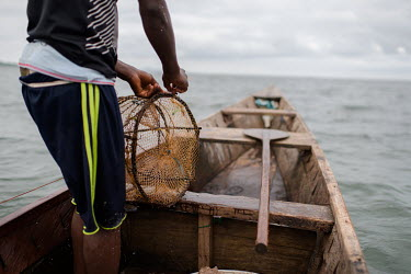 Vincent Oletey, repairs a fish trap while working as boat crew on Lake Volta.  Vincent (14) and Noah (12) spend up to six nights a week working on fishing canoes on Lake Volta. Rising at 03:00am, th...