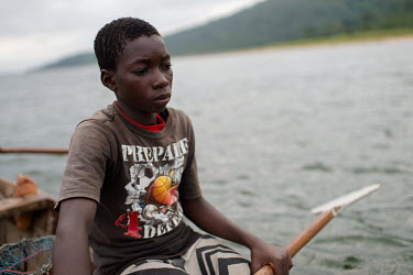 Noah Oletey waiting for his brother (not pictured) to finish emptying a fish trap on Lake Volta before they paddle on to the next one.  Boat crew Vincent (14) and Noah Oletey (12) spend up to six nigh...