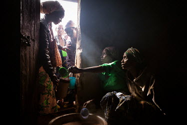 Two volunteers serve up porridge to young mothers at Antionette' porridge club. Antionette (standing in the door way) is an accountancy graduate who was inspired to start the clubs when she saw that c...