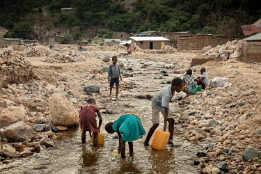 People gather to wash and collect water from the Mulongwe River after it had receded in the days after heavy rains caused it to break its banks. The ensuing floods caused significant material damage w...