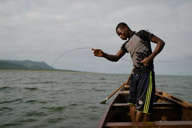 Vincent Oletey hauls up fish traps while working as boat crew on Lake Volta.  Vincent (14) and his brother, Noah (12), spend up to six nights a week working on fishing canoes on Lake Volta. Rising at...