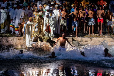 As priests bless the water at the Fasiladas Baths during Timkat (a celebration of the baptism of Jesus and the Orthodox Epiphany) pilgrims begin to jump into the water to purify themselves. The offici...