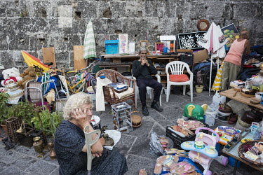 Retired people selling second hand items in an alley in the historical centre of Rhodes.