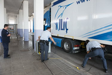Border police agents check a Turkish truck using heartbeat detectors at the Kipoi border post.