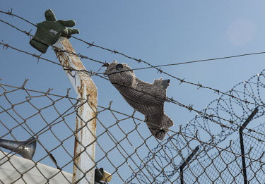A cap and glove caught in the barbed wire surrounding a detention centre for illegal migrants.