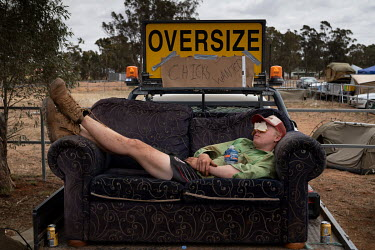 Jack Manning (19) places a slice of white bread over his eyes to help himself sleep on a couch on the back of a pick up truck ('Ute') at the Ariah Park, Bachelor and Spinster ball.   Known to locals...