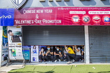 Staff at an electronics shops crouch in the partially shuttered entrance and watch as protestors, including student activists and factory workers, march in a show support for the NLD (National League...