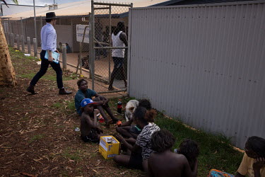 North Australian Aboriginal Justice Agency Lawyer (NAJA) John Blackley walks through the entrance of the Wadeye police station and courthouse, past a group of women and children sitting outside.  Nort...