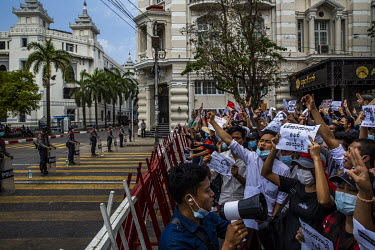 Police officers stand behind a barrier as protestors gather near the city hall to show their support for the NLD (National League for Democracy), Aung San Suu Kyi and democracy and to protest the 1 Fe...