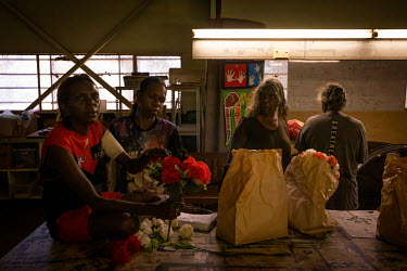 Clare Jongmin (3rd from the right) prepares flowers and other memorial objects with her family, at the Wadeye women's centre, before the funeral of a relative. Clare Jongmin's nephew was shot and kill...